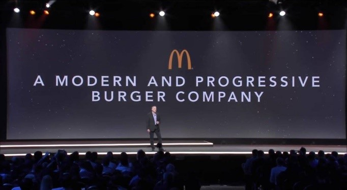 "Photo of a CEO on stage under the McDonalds logo and a banner read, ""A MODERN AND PROGRESSIVE BURGER COMPANY"""